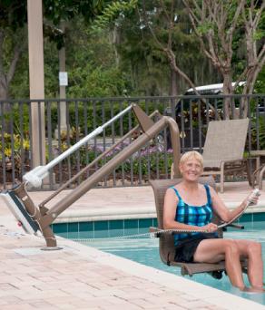 mujer mayor en pisina con asiento para descenso acuatico